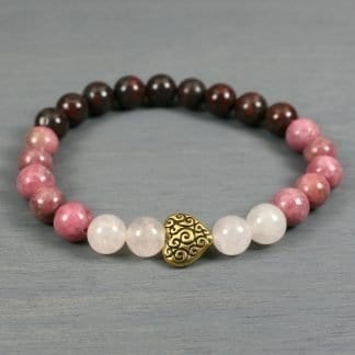 Ombre rose quartz, rhodonite, and brecciated jasper stretch bracelet with an antiqued gold plated heart focal bead with scrollwork detailing